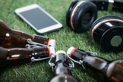 Пивные бутылки при smartphone и наушники лежа на траве Стоковое Фото