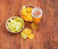 Пиво лагера и 2 различных картофельной стружки на старой таблице Стоковые Изображения