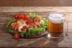 Пиво в прозрачной кружке и загонщиках цыпленка в беконе на древесине Стоковое фото RF