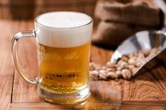 Пиво в стекле кружки с фасолью на деревянной таблице Стоковые Фото