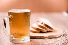 Пиво в стекле кружки с хлебом на деревянной таблице Стоковые Изображения RF