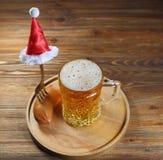 Пиво в стеклянных кружке и сосиске с вилкой с вилкой в крышке рождества Стоковая Фотография RF