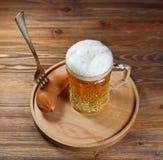Пиво в стеклянных кружке и сосиске с вилкой Стоковая Фотография RF