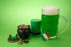 Пиво зеленого цвета дня ` s St. Patrick с shamrock, баком с золотыми монетками, подковой и шляпой лепрекона против зеленой предпо Стоковое Фото
