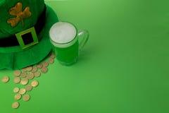 Пиво зеленого цвета дня ` s St. Patrick с shamrock, баком с золотыми монетками, подковой и шляпой лепрекона против зеленой предпо Стоковое Изображение RF