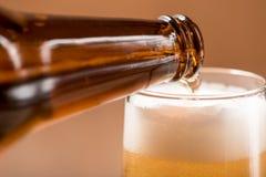 Пиво лить от верхней части в бутылке на деревянной таблице Стоковые Изображения RF