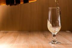 Пиво лить от верхней части в бутылке на деревянной таблице Стоковое фото RF