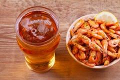 Пиво и креветки в шаре на деревянной предпосылке Стекло пива и креветок aleppo стоковое фото rf