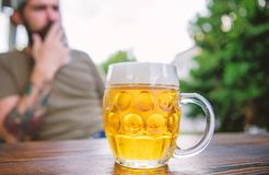 Пиво кружки холодное свежее на конце таблицы вверх Человек сидит терраса кафа наслаждаясь пивом defocused Концепция алкоголя и ба стоковая фотография