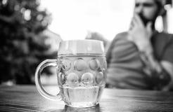 Пиво кружки холодное свежее на конце таблицы вверх Человек сидит терраса кафа наслаждаясь пивом defocused Концепция алкоголя и ба стоковое изображение
