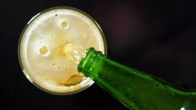 Пиво лить в стеклянное замедленное движение на черной предпосылке сток-видео