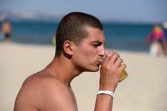 Пиво молодого красивого sporty человека выпивая на пляже в summerti стоковое фото rf