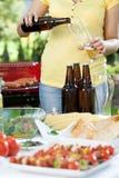 Пиво молодой женщины лить стоковые фотографии rf