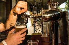 Пиво мужского бармена лить в стеклянный конец-вверх r стоковые фото