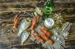 Пиво с пеной в стекле и бутылке пива с закуской кипеть рыб craw и высушенных посоленных рыб Стоковая Фотография RF