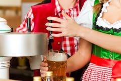 Пиво чертежа молодой женщины в ресторане или пабе Стоковое Фото