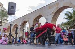 Пиво-Sheva, ИЗРАИЛЬ - 5-ое марта 2015: Волшебник выполняет на встрече гипнозом сцены улицы с девушкой в красном цвете - Purim Стоковые Фотографии RF