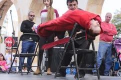 Пиво-Sheva, ИЗРАИЛЬ - 5-ое марта 2015: Волшебник выполняет на встрече гипнозом сцены улицы с девушкой в красном цвете - Purim Стоковые Изображения RF