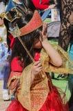 Пиво-Sheva, ИЗРАИЛЬ - 5-ое марта 2015: Девушка в красном платье с красной кроной при длинные волосы стоя в профиле, ее сторона в  Стоковые Фото