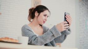 Пижамы милой женщины нося имея завтрак и используя технологию smartphone в кухне Привлекательная женщина делает selfie Стоковая Фотография