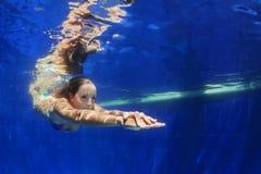 Пикирование молодой женщины подводное в голубом бассейне стоковые изображения rf