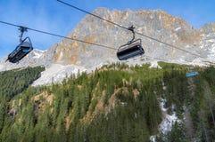 Пики Альпов скалистые и подъемы лыжи над лесом Стоковая Фотография RF