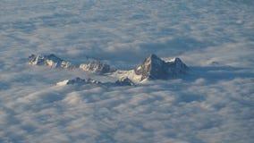 Пики гор поднимают вне от облаков которые покрывают землю Ландшафт от окна самолета стоковое фото rf