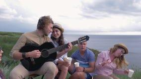 Пикник, компания веселых мальчиков друзей и девушки играют гитару и поют песни пока воссоздание природы около реки сток-видео