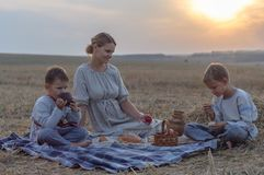 Пикник семьи в природе мать и дети едят на склоняя пшеничном поле стоковое фото rf