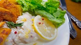 Пикши испеченные лимоном с зажаренными картошками Sause лимона, Стоковые Фото