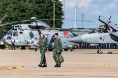 2 пилота военно-воздушных сил Великобритании идя через гудронированное шоссе на RAF Waddington при воздушные судн сидя на заднем  стоковая фотография rf