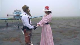 Пилот в шлеме и девушка в розовых платье и шляпе держат руки на предпосылке старого самолета акции видеоматериалы
