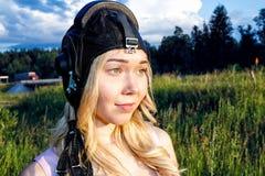 Пилот девушки в шлеме полета в лете на предпосылке зеленой травы в солнечном дне стоковые изображения rf