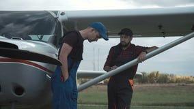 Пилот и механик беседуя на авиаполе акции видеоматериалы