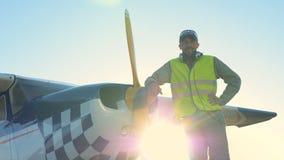 Пилот около небольшого самолета, стоя с наушниками на взлетно-посадочной дорожке акции видеоматериалы