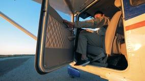 Пилот сидит в арене cropduster, подмигивает и закрывает двери видеоматериал