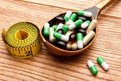 Пилюльки в ложке медицины в деревянной ложке стоковое изображение rf