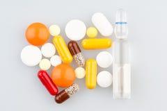 Пилюльки и ампула на медицинской таблице Стоковое Изображение RF