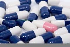 пилюльки капсулы предпосылки голубые pink белизна Стоковое Фото