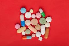 Пилюльки лекарства сортированные на красной предпосылке Стоковые Фотографии RF