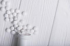 Пилюльки медицины на белой таблице Стоковые Изображения
