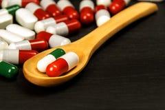 Пилюльки на ложке Продажа медицин Доза лекарств Анаболические стероиды на таблице стоковые фото
