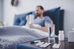 Пилюльки на таблице с больным человеком в кровати Стоковые Фото