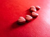 Пилюльки сердца в красной предпосылке красный цвет поднял Стоковые Фото