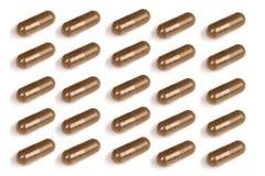 Пилюльки темного коричневого цвета изолированные на белой предпосылке Стоковые Фото