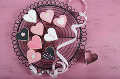 Пинк, черно-белые домодельные печенья формы сердца на винтажной затрапезной шикарной розовой деревянной предпосылке Стоковые Фото