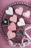 Пинк, черно-белые домодельные печенья формы сердца на винтажной затрапезной шикарной розовой деревянной предпосылке Стоковое Фото