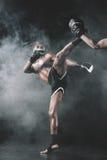 Пинок бойца Muay тайский практикуя на черноте Стоковые Изображения