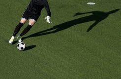 Пинок голкипера футболиста шарик во время футбольного матча стоковое фото