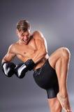 Пинок колена красивого мышечного бойца практикуя Концепция боевых искусств Стоковые Фото